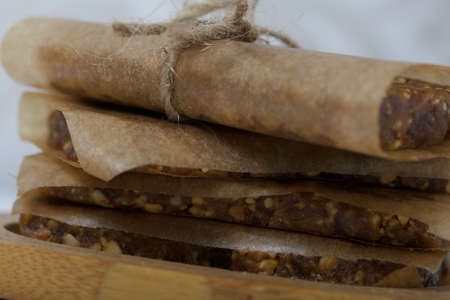 Nut & Dried Fruit Energy Bars. Wrapped in paper and tied with twine. Nearby a skein of twine. Close-up shot.