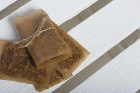 Homemade Nut & Dried Fruit Energy Bars. Wrapped in paper and tied with twine. On a white wooden box.
