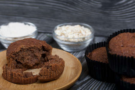 Oatmeal chocolate muffins. Drawn up on a silver platter. One is broken to show a cut. On black pine boards.