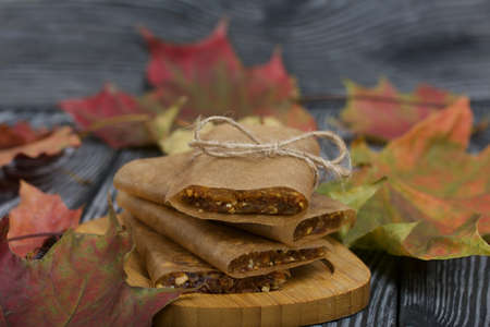 Homemade Nut & Dried Fruit Energy Bars. Wrapped in paper and tied with twine. Nearby autumn maple leaves.