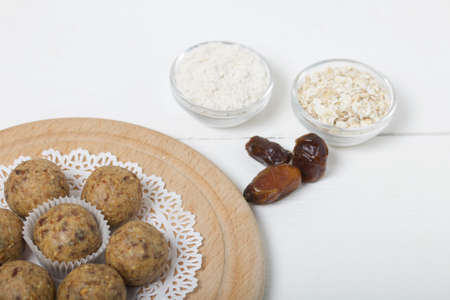 Dried fruit and oatmeal sweets. Nearby ingredients for their preparation. On a white wooden box.