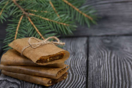 Homemade Nut & Dried Fruit Energy Bars. Wrapped in paper and tied with twine. Nearby there are fir branches. Close-up shot.