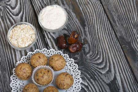 Dried fruit and oatmeal sweets. Nearby ingredients for their preparation. On black pine boards.