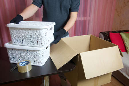 The man puts things in a cardboard box. Moving to a new place of residence.