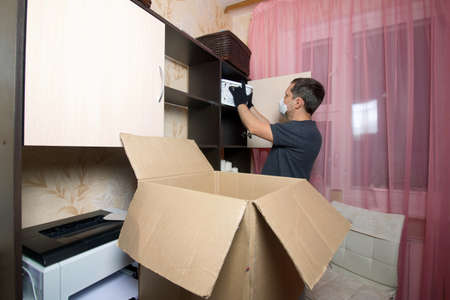 The man takes boxes off the shelves and puts them in a cardboard box. Moving to a new place of residence. Reklamní fotografie