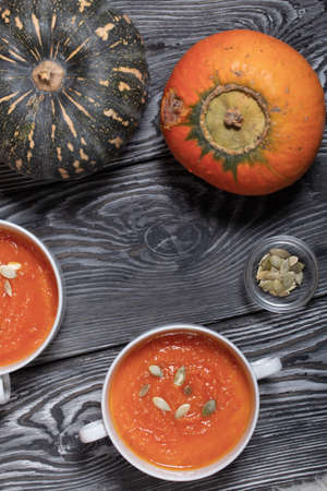 Pumpkin tomato cream soup. With the addition of pumpkin seeds. Several pumpkins are nearby. View from above. On pine boards.