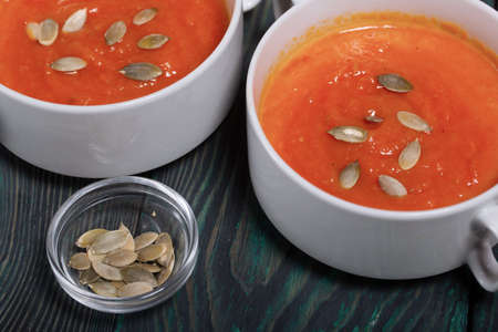 Pumpkin tomato cream soup. With the addition of pumpkin seeds. On pine boards.