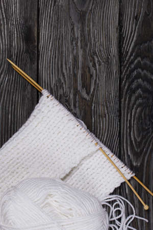 Knitting with needles. Wooden knitting needles and white threads. On black pine boards.
