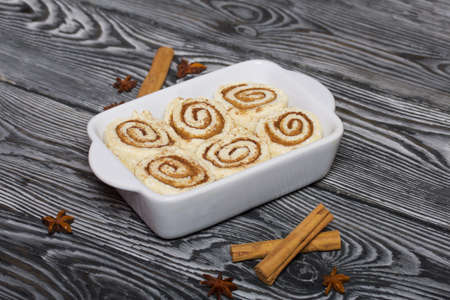 Baking cinnabons. The cinnamon dough is in the baking dish. Next to it are cinnamon sticks and anise stars. On pine boards in black.