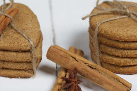 Gingerbread cookies tied with twine. Nearby are cinnamon sticks and anise stars. On boards painted white. Close-up shot.