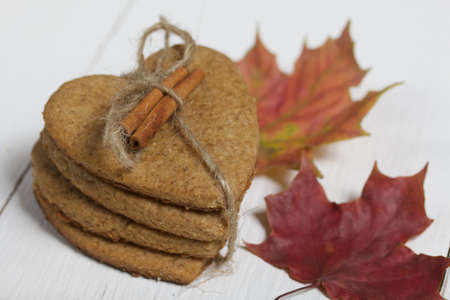 Gingerbread cookies tied with twine and autumn maple leaves. On boards painted white. Close-up shot.