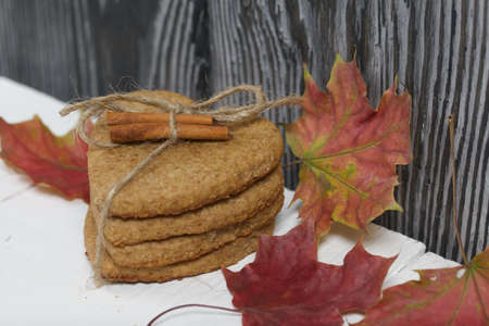 Gingerbread cookies tied with twine and autumn maple leaves. On boards painted white.