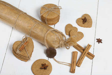 Gingerbread cookies tied with twine and spices. On boards painted white. Filmed from above.