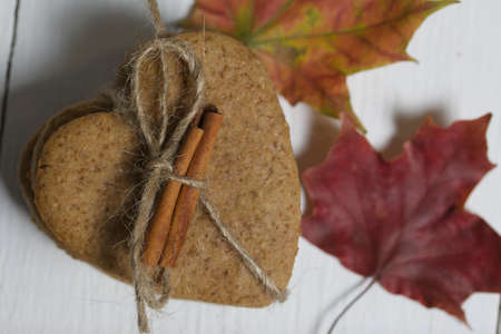Gingerbread cookies tied with twine and autumn maple leaves. On boards painted white. Close-up shot. 写真素材