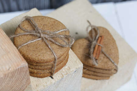 Gingerbread cookies tied with twine. Nearby are wooden blocks. On boards painted white.