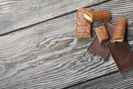 Chopped up chocolate bar. Filled with caramel and nuts. Nearby are pieces of chocolate. On black pine boards. 写真素材