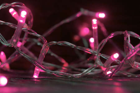 Burning garland with pink lights. Burns in the dark. Close-up shot.