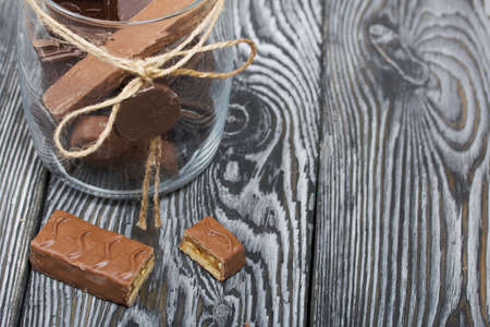 Chopped up chocolate bar. Filled with caramel and nuts. Nearby is a glass jar with chocolates. On black pine boards.