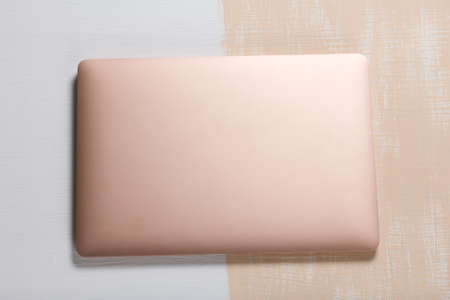 The laptop is pink. The surface is painted in white and beige. Filmed from above. 写真素材