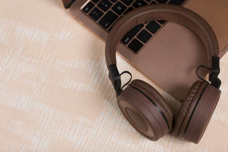 Fragment of an open pink laptop. Nearby are wireless headphones in brown. The surface is painted in white and beige.