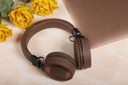 Fragment of a pink notebook. Nearby are brown wireless headphones and yellow roses. The surface is painted in white and beige.