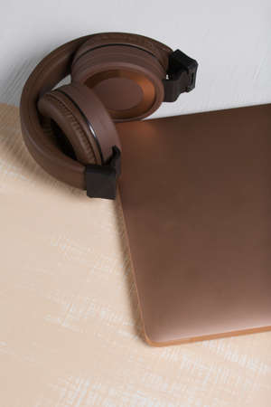 Fragment of a pink notebook. Nearby are wireless headphones in brown. The surface is painted in white and beige.