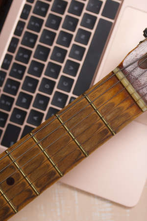 Fragment of acoustic guitar and notebook. Against a background painted in white and beige.