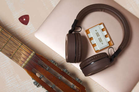 Fragment of acoustic guitar and notebook. Nearby are wireless headphones, a tuning fork and a pick. Against a background painted in white and beige.
