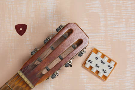 Acoustic guitar neck, tuning fork and pick. Against a background painted in white and beige. 写真素材