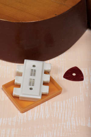Fragment of acoustic guitar, tuning fork and pick. Against a background painted in white and beige.