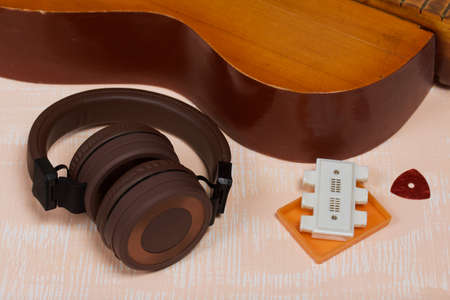 Fragment of acoustic guitar, tuning fork and pick. Nearby are wireless headphones. Against a background painted in white and beige.