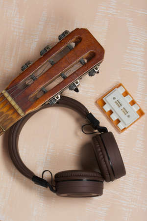 Fragment of acoustic guitar and tuning fork. Nearby are wireless headphones. Against a background painted in white and beige. 写真素材