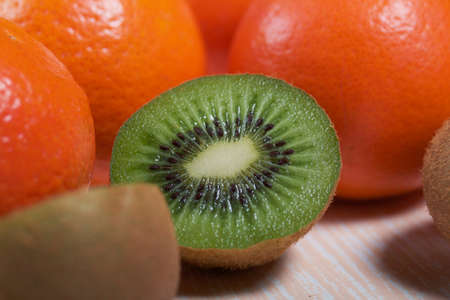 Several orange tangerines. Kiwi fruit cut in half. Juicy green flesh is visible. Close-up shot. Lie on a beige surface.