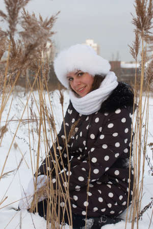 Young woman on a walk in winter. Dressed in winter clothes. She sat down among the tall, dried grass. There is a lot of snow around. Imagens