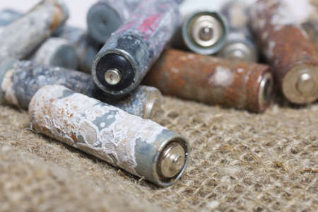 Corroded used batteries. Nearby is linen. Close-up shot.