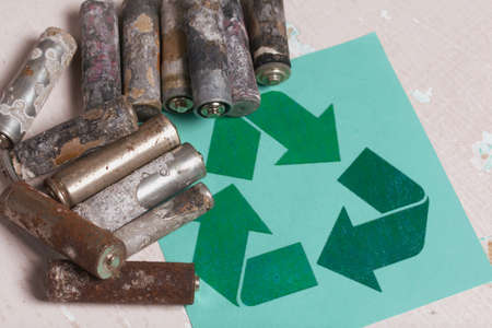 Corroded used batteries. Nearby is a waste recycling sign. Close-up shot.
