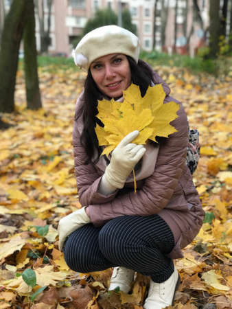 Portrait of a girl in the autumn park. In her hand the girl holds a bouquet of yellow maple leaves. There are many fallen autumn leaves around. Zdjęcie Seryjne