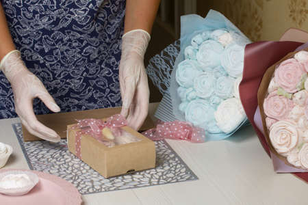 A woman is packing marshmallows in craft packaging. Ties a ribbon on a bow. Nearby are bouquets of marshmallow roses and tulips. Zdjęcie Seryjne