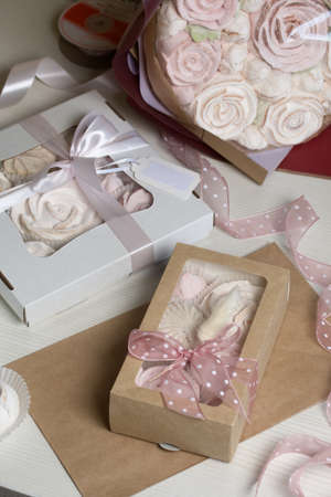Homemade marshmallows in craft packages. Zephyr in the form of a rose. Decorated with ribbons. Close-up shot. Zdjęcie Seryjne