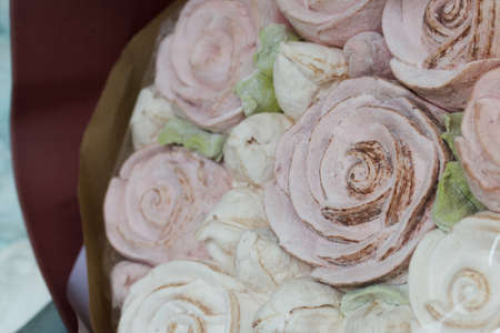Marshmallow bouquets in craft packaging. Consist of marshmallow roses and tulips. The bouquets lie on the table surface. Close-up shot.