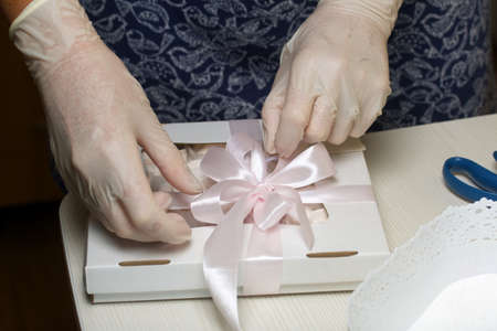 A woman is packing marshmallows in craft packaging. Ties a ribbon on a bow. Close-up shot.