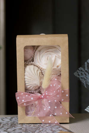 Homemade marshmallows in craft packaging. Zephyr in the form of a rose. Decorated with ribbon and lagurus. Close-up shot.