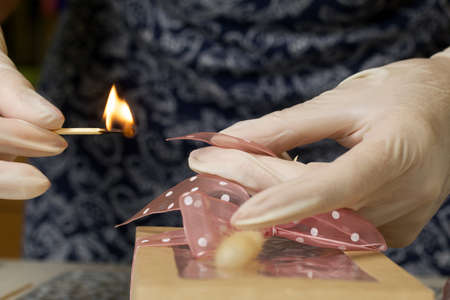 A woman is packing marshmallows in craft packaging. He cauterizes the tape with a match. Nearby are bouquets of marshmallow roses and tulips. Close-up shot.