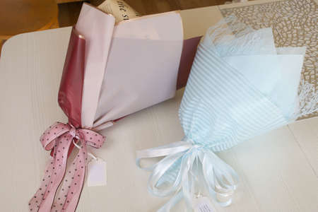 Bouquets in craft packaging. Tied with a ribbon tied to a bow. Close-up shot.