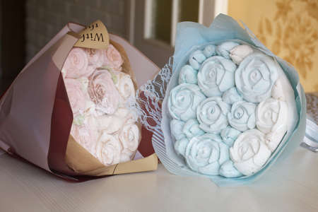 Marshmallow bouquets in craft packaging. Consist of marshmallow roses and tulips. The bouquets lie on the table surface.