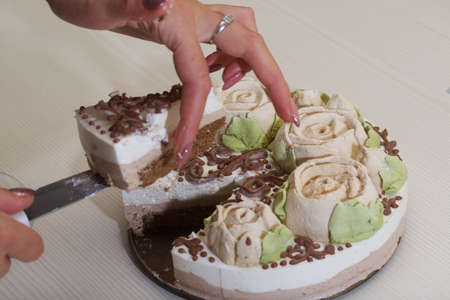 A woman cuts a bird's milk cake, decorated with marshmallow roses and chocolate.