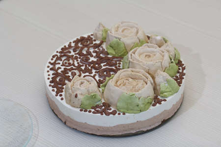 Bird's milk cake decorated with marshmallow roses and chocolate.