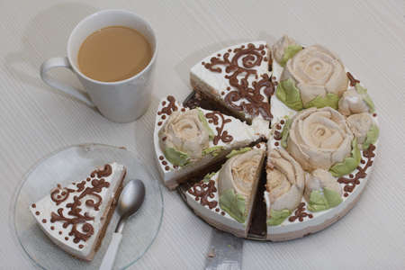 Bird's milk cake decorated with marshmallow roses and chocolate. Cut into pieces. Nearby is a cup of coffee with milk.