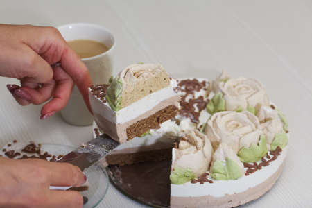 A woman cuts a bird's milk cake, decorated with marshmallow roses and chocolate. Nearby is a cup of coffee with milk.