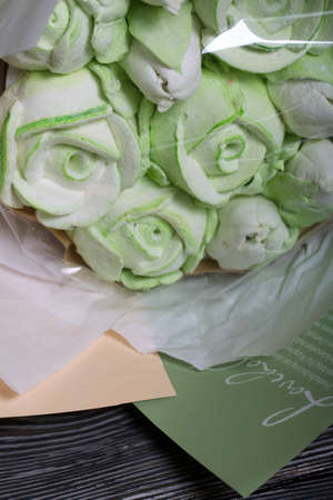 Marshmallow bouquet in paper packaging. Zephyr in the form of roses and tulips. In light green colors. Close-up shot. Zdjęcie Seryjne